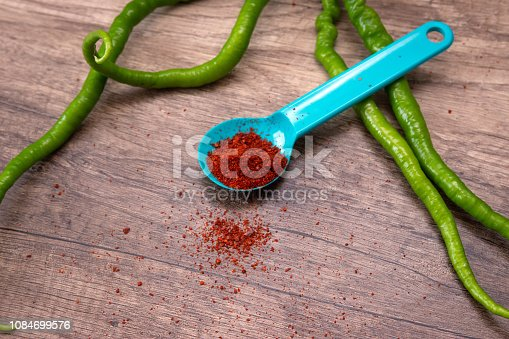 istock Homemade Dried and Crushed Chili Pepper with Herb and Spices in Wooden Spoon isolated on wooden background.Green chili pepper. 1084699576