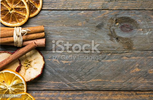 istock Homemade dried fruits slices of orange apple cinnamon sticks on on old plank wood background. New year Christmas decoration elements vintage style card poster. Ingredients for mulled wine tea 1165228407