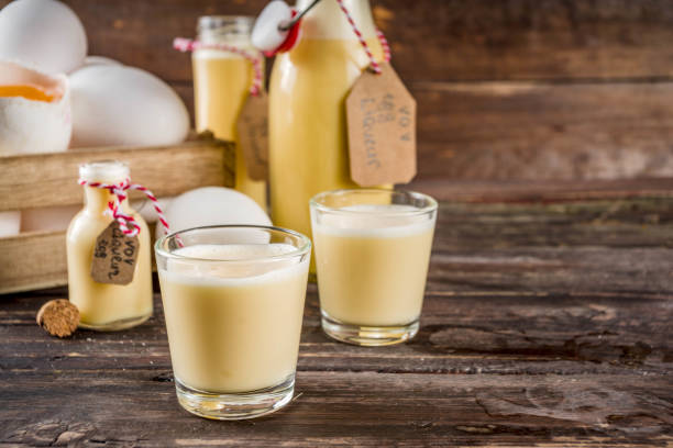 Homemade egg liquor Traditional Italian Vov eggs liquor. German Egg Liqueur Eierlikor. In different bottle and shot glasses, Wooden background copy space pisco peru stock pictures, royalty-free photos & images