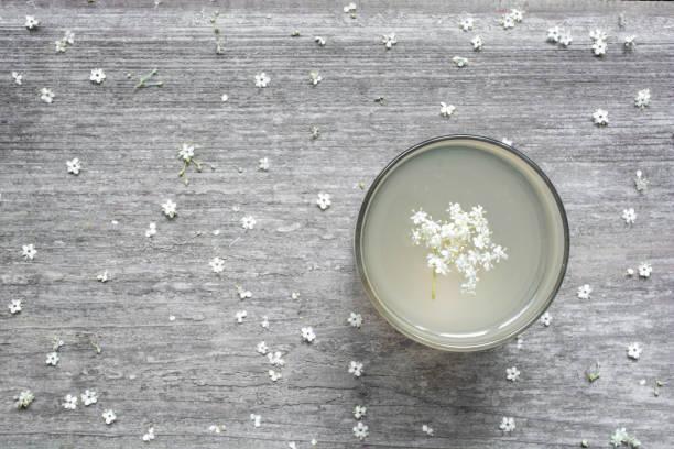 hausgemachter holunderblüten sirup mit blumen auf weißer holztisch. gesunden pflanzliches getränk. - holunderlikör stock-fotos und bilder