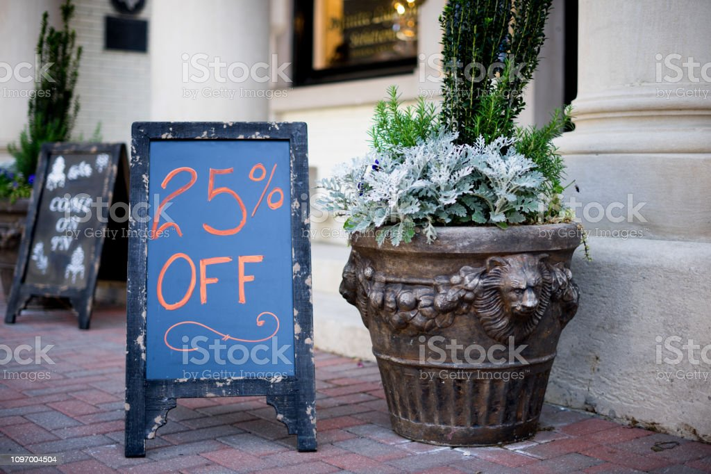 Homemade farmhouse style chalkboard 25% off sign outside a small business stock photo
