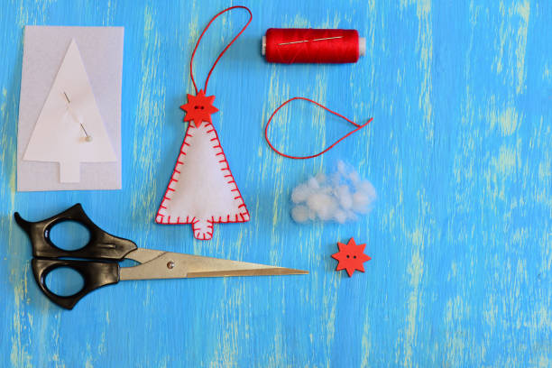 homemade fühlte, weihnachtsbaum, papier-vorlage, filz, faden, nadel, stift, schere auf einem hölzernen hintergrund mit textfreiraum. legen sie für weihnachtsdekoration. nähen-kreativität für kinder. tutorial. ansicht von oben - diy xmas stock-fotos und bilder