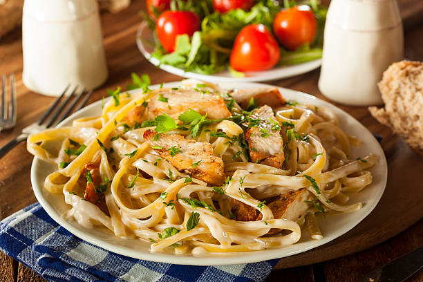 Homemade Fettucini Aflredo Pasta Homemade Fettucini Aflredo Pasta with Chicken and Parsley chicken stock pictures, royalty-free photos & images