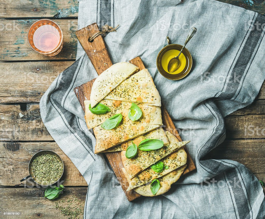 Homemade focaccia flatbread with basil, olive oil and rose wine stock photo