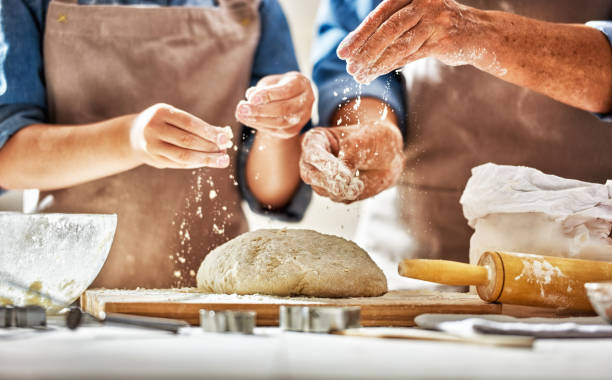 Homemade food and little helper Close up view of bakers are working. Homemade bread. Hands preparing dough on wooden table. yeast stock pictures, royalty-free photos & images