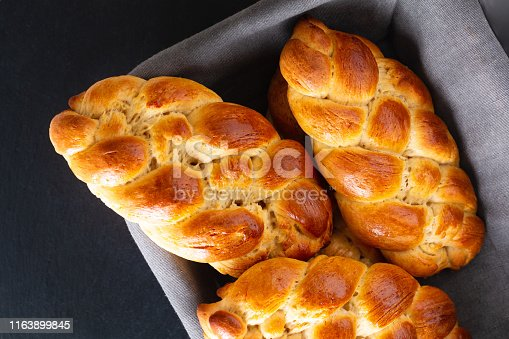 Homemade food concept fresh baked bread braid challah dough in bread basket with copy space