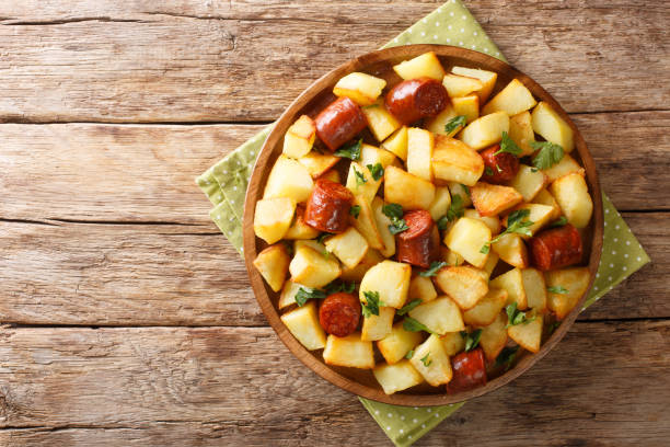 Homemade food fried potatoes with sausages and herbs close-up in a plate. Horizontal top view stock photo
