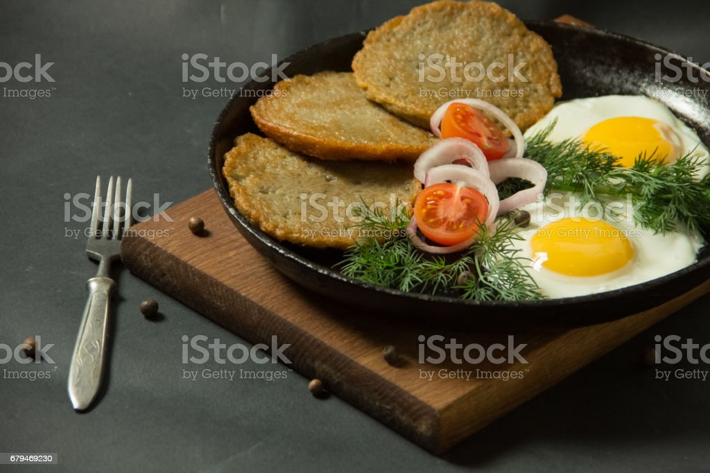 Homemade food. Tasty breakfast. Appetizing fried egg with potato pancakes and herbs in dripping pan  on a black background royalty-free stock photo