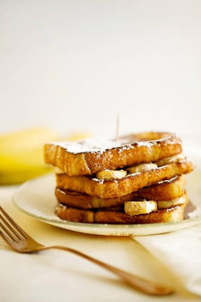 hausgemachte french toast von weizenbrot mit bananen und honig auf einem hellen hintergrund nahaufnahme. gesunder snack brot und obst zum frühstück und brunch. frisch nach hause backen. textfreiraum - gebackene banane stock-fotos und bilder