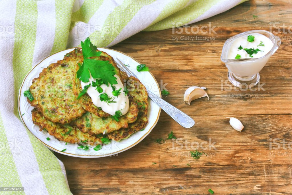 homemade fried fritters of zucchini with sour cream sauce stock photo