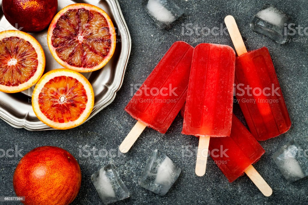 Homemade frozen blood orange natural juice alcoholic popsicles - paletas - ice pops. Overhead, flat lay, top view, zbiór zdjęć royalty-free