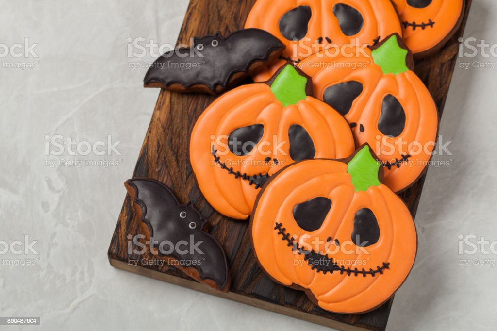 Homemade ginger cookies in the shape of pumpkins and bats on Halloween. On the lighter concrete background. Top view stock photo