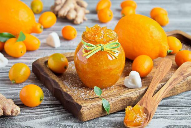 Homemade ginger, lemon and kumquat jam in a glass jar stock photo