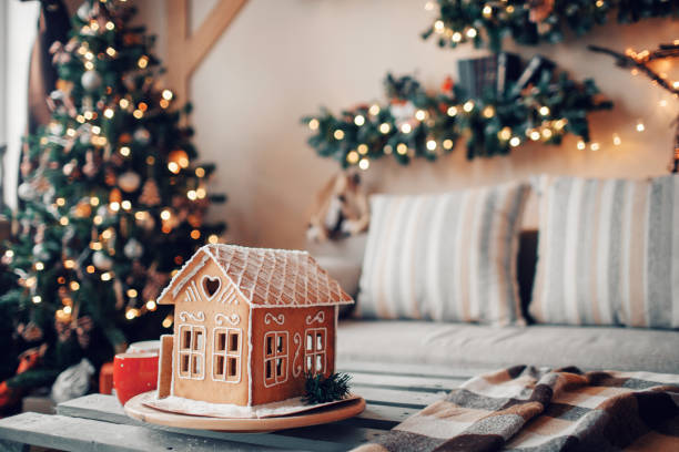 homemade gingerbread house on light room background - decorating stock photos and pictures