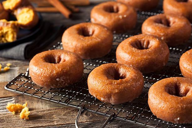 homemade glazed autumn pumpkin donuts - hausgemachte gebackene donuts stock-fotos und bilder