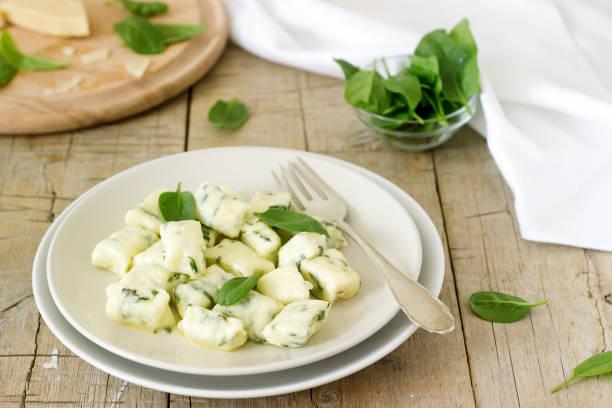 hausgemachte gnocchi mit ricotta, käse und spinat auf eine leichte platte. - ricotta stock-fotos und bilder