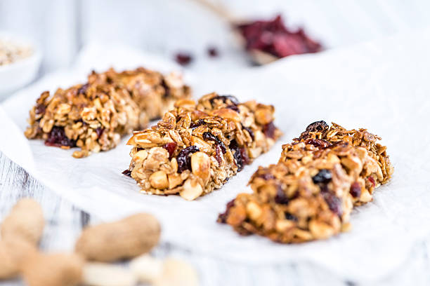 Homemade Granola Bars with Peanuts and Cranberries (selective fo Homemade Granola Bars with Peanuts and Cranberries (selective focus) as detailed close-up shot homemade stock pictures, royalty-free photos & images
