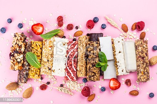 Assortment of different granola cereal bars on pink background. Healthy pre or post workout snacks with fruits, nuts and berries. Copy space. Top view