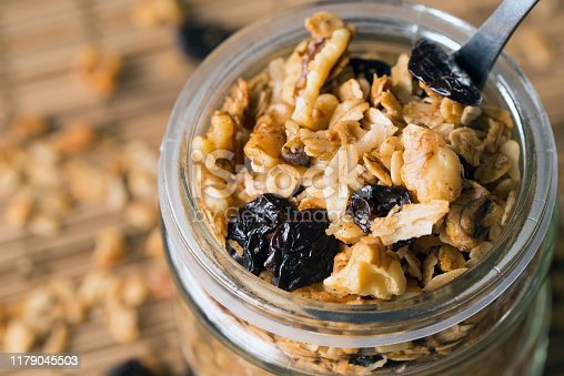 Homemade granola in a glass jar with selective focus, healthy vegan snack