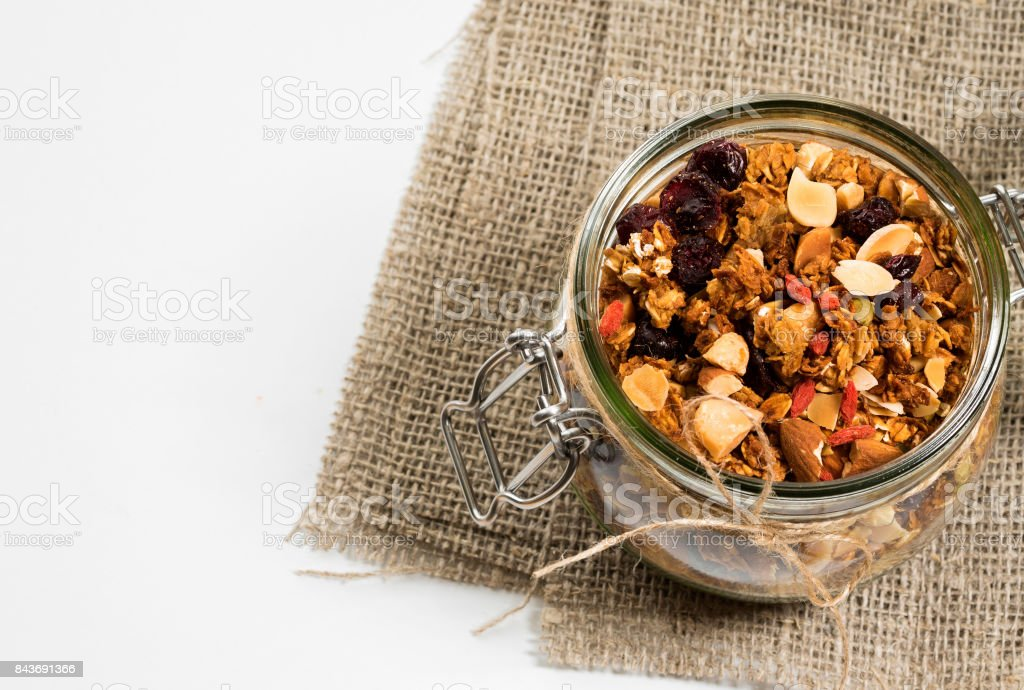 Homemade granola in open glass jar on rustic wooden background stock photo