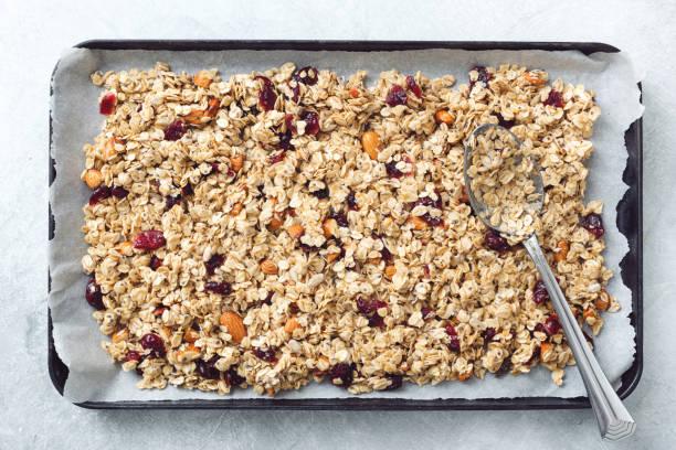 homemade granola on baking sheet - granola imagens e fotografias de stock
