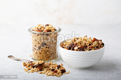 Homemade granola with coconut, raisins and almonds for breakfast in a jar and a bowl