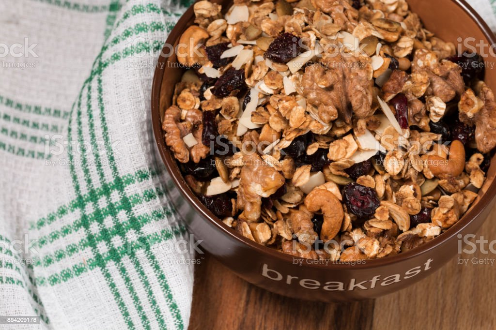 Homemade granola with honey, oatmeal, cashew nut, almond, pistachio, raisin and cranberry in clay bowl,glass with milk on wood dark table, royalty-free stock photo