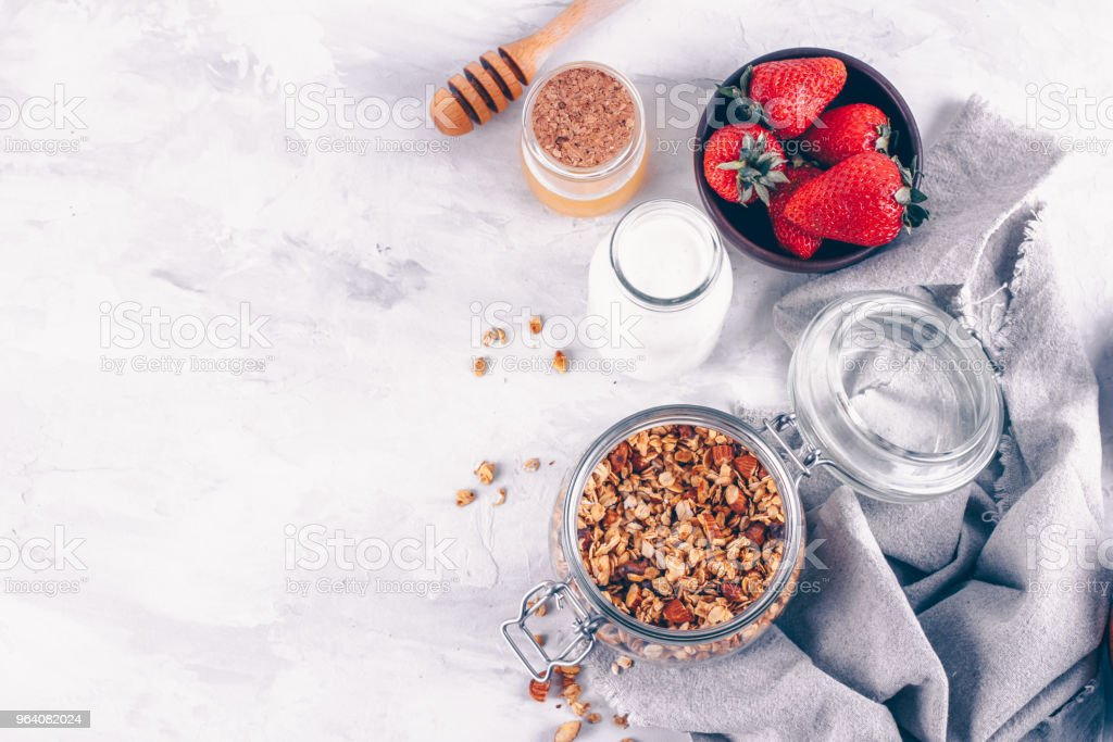 Homemade granola with yogurt, strawberries and honey on white marble table background from top view, above. Breakfast Diet Clean Food - Royalty-free Almond Stock Photo