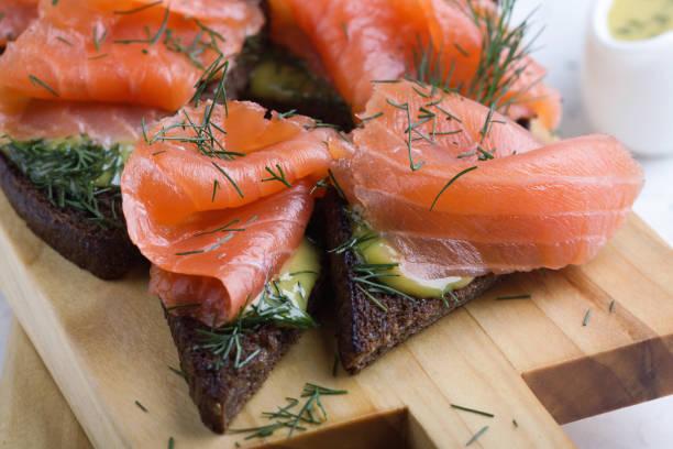 Hausgemachter Graved Lachs, geräucherter Lachs mit Senfsauce und Dill auf geröstetem Schwarzbrot – Foto