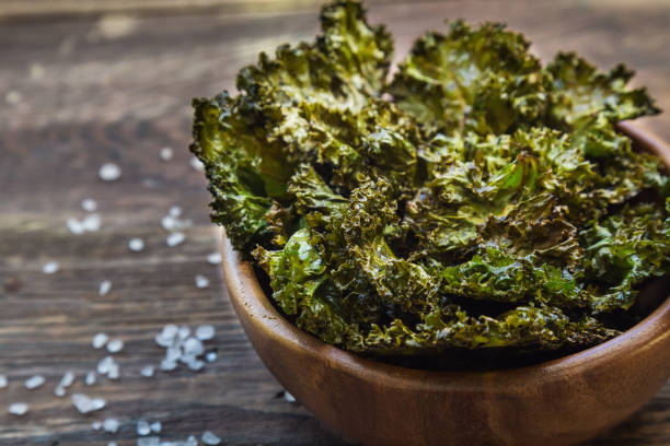 Homemade green kale chips baked with balsamic vinegar in bowl on rustic wooden background Healthy snack. Selective focus. kale stock pictures, royalty-free photos & images