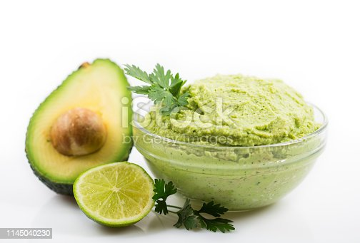 Homemade guacamole dip in the bowl on the white background