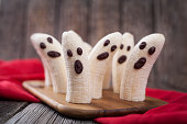 Homemade halloween scary banana ghosts monsters with chocolate faces. Healthy