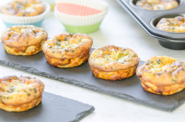 Homemade ham and cheese mini tarts in a muffin style Homemade tartlets filled with ham, cheese , green onions, baked in muffin tin and served on a slate plate for a brunch or breakfast muffin tin stock pictures, royalty-free photos & images