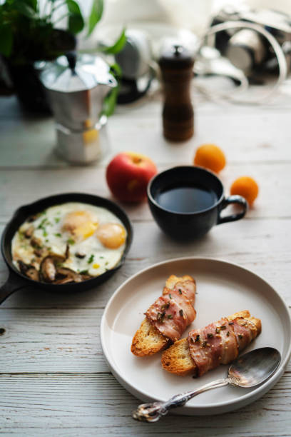 homemade healthy breakfast: bacon rolled toast, cheese roasted mushroom and egg stock photo