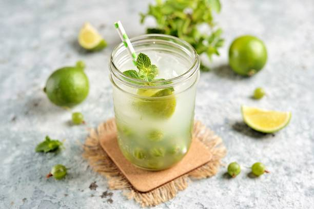 Homemade healthy non-alcoholic cocktail Mojito from green gooseberry, lime and mint. stock photo