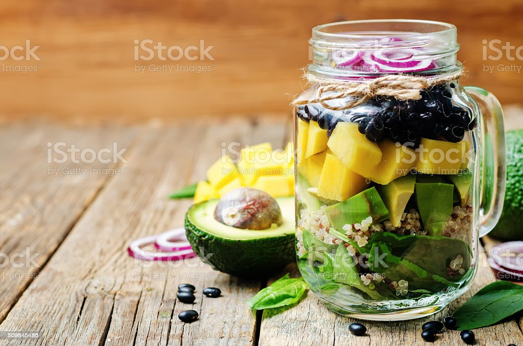 homemade healthy salads with black beans, vegetables, fruits, and quinoa stock photo