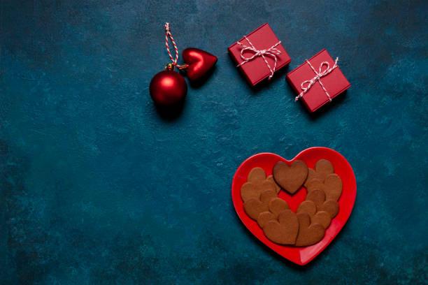 Caseiro Heart Shape Gingerbreads Prato de forma do coração vermelho e duas caixas de presente no fundo Clássico Azul. Vista de cima, close-up. Natal, conceito de Ano Novo - foto de acervo