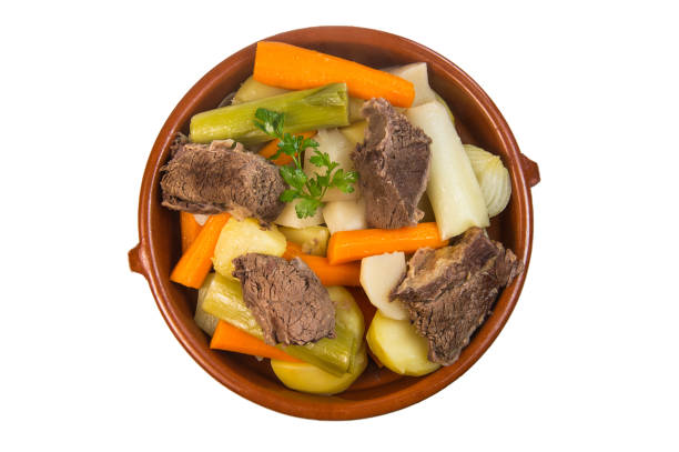Homemade hot beef soup with vegetables close up in a bowl on white Homemade hot beef soup with vegetables close up in a bowl on white background pot au feu stock pictures, royalty-free photos & images