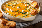 istock Homemade hot buffalo chicken dip with crostini close up in baking dish. horizontal 1051095650