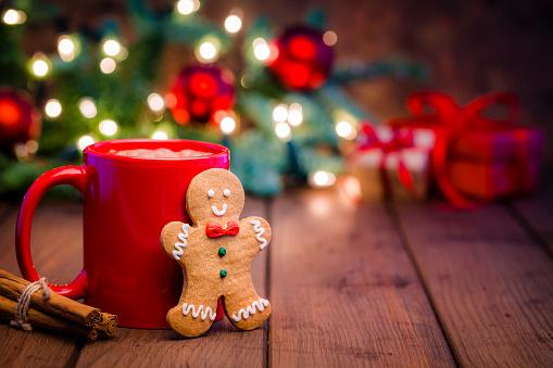 Homemade hot chocolate mug and gingerbread cookie on Christmas table