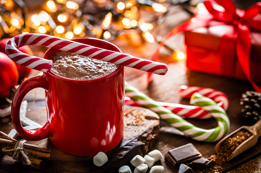 Homemade hot chocolate mug with red and white candy cane on rustic wooden Christmas table