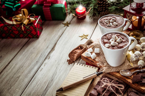 Homemade hot chocolate mugs with marshmallows on rustic wooden table with candlelight and note pad. Christmas themes. Christmas table setup with two homemade chocolate mugs with marshmallows and candlelight. Copy Space. navidad stock pictures, royalty-free photos & images