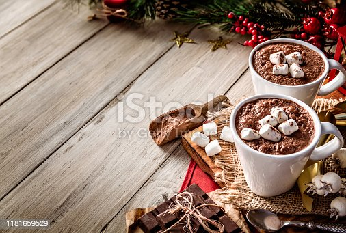 Homemade hot chocolate mugs with marshmallows on rustic wooden table. Christmas themes. Copy Space.