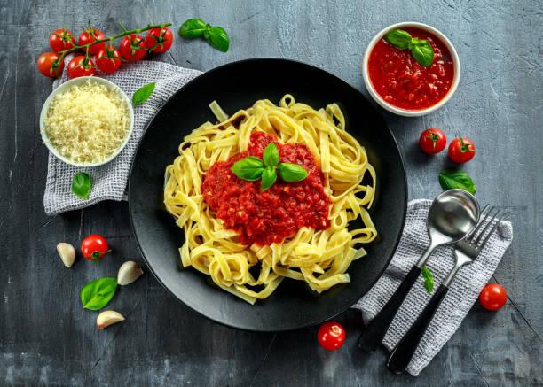 hausgemachte heiße pasta mit marinara sauce, basilikum, knoblauch, tomaten, parmesan-käse auf platte. - roten küchentische stock-fotos und bilder