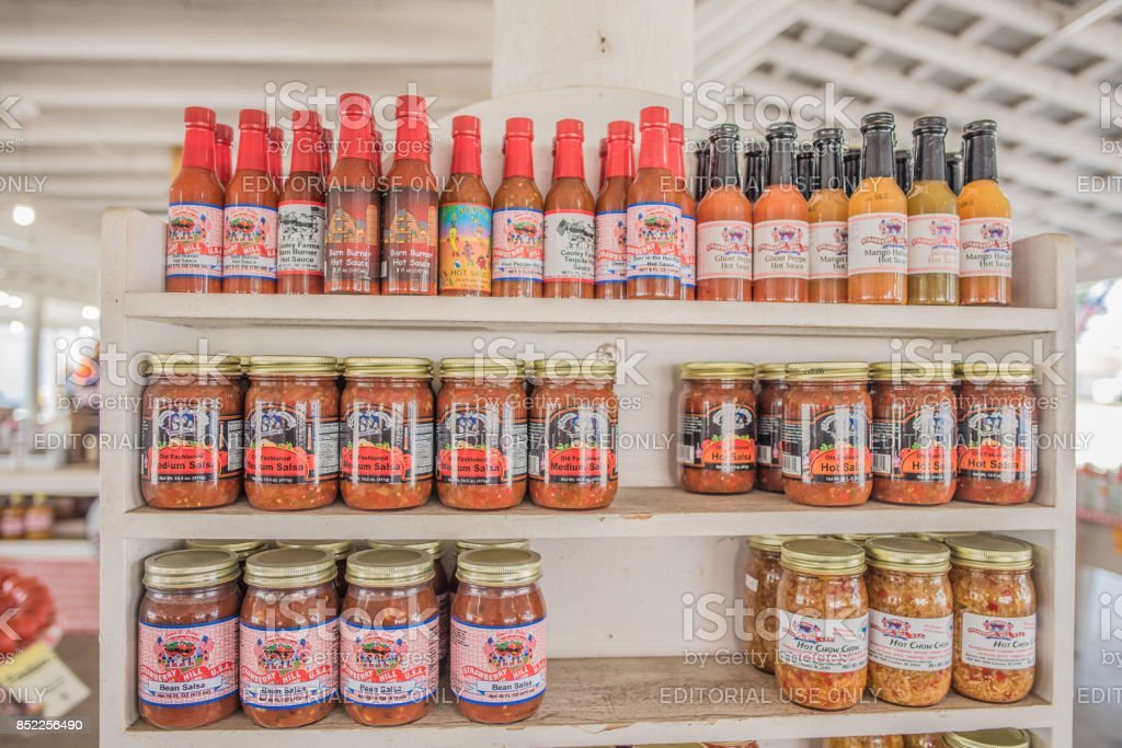 Homemade hot sauce for sale at local farmers market in South Carolina Cooley Springs, South Carolina, Sept. 10, 2017: Fresh salsa and hot sauce for sale at Strawberry Hill market in Cooley Springs, S.C. a beautiful area known for farms of peaches and other crops upstate Animal Wildlife Stock Photo