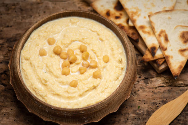 Homemade hummus dipping sauce with chickpeas and food ingredients Homemade hummus dipping sauce with chickpeas and food ingredients in a bowl on the table tabletop view cicer arietinum plant stock pictures, royalty-free photos & images