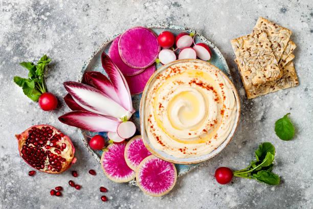 Hausgemachter Hummus, gewürzt mit Olivenöl und Paprika und frischem Gemüse: Wassermelone Rettich, Radieschen, rote Chicorée, Granatapfel. Gesunde vegetarische Vorspeise oder Snack Platte – Foto