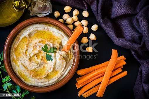 Top view of a homemade hummus surrounded by the ingredients for cooking and seasoning the dipping sauce like chick peas, garlic, parsley, and olive oil alongside a heap of carro sticks on a black background. Low key DSLR photo taken with Canon EOS 6D Mark II and Canon EF 24-105 mm f/4L