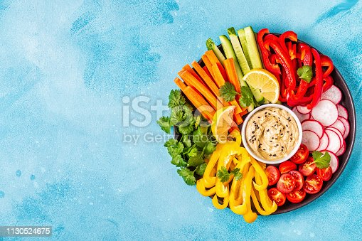 Homemade hummus with fresh vegetables, top view.