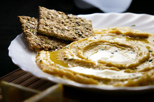Homemade hummus with lemon, herbs, virgin olive oil and integral flatbread stock photo